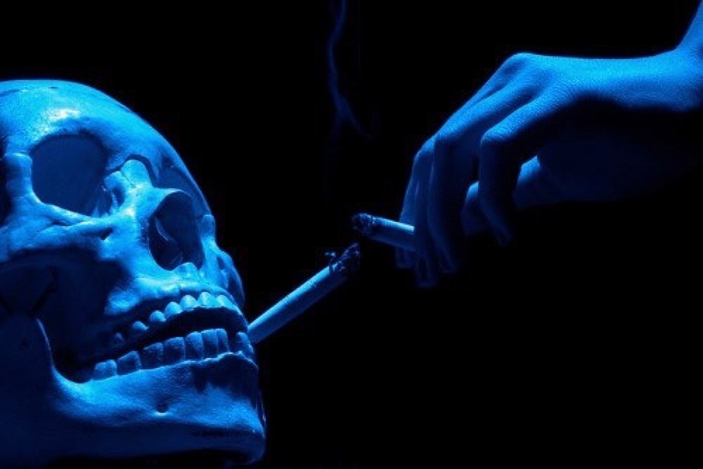 AN IMAGE SHOWING A SKELETON SMOKING A CIGARETTE, IMPLYING THAT EVEN AFTER DEATH WE WILL INDULGE IN THAT WHICH KILLS US. MUCH LIKE THE PERSON I WAS